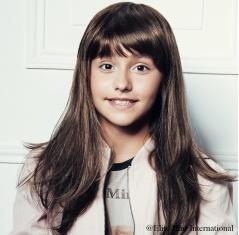 Portrait d'une ado portant la chevelure Captive Juniors, en brun, cheveux de synthèse d'Elite Hair International